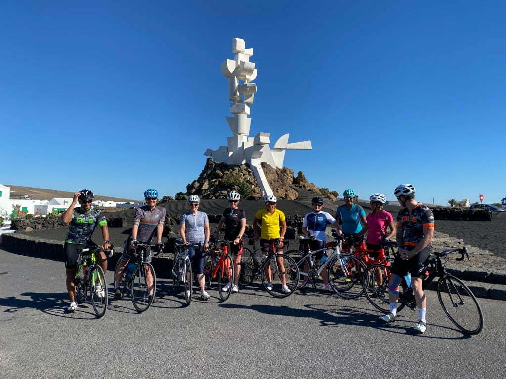 A group of cyclists pose in front of a statue